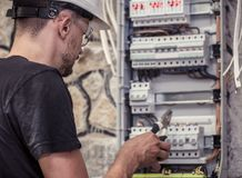 A male electrician works in a switchboard with an electrical con. Necting cable, connects the equipment with tools, the concept of complex work, space for text Stock Photos