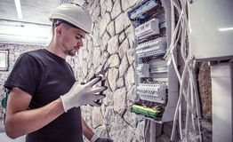 A male electrician works in a switchboard with an electrical con. Necting cable, connects the equipment with tools, the concept of complex work, space for text Stock Image