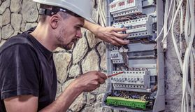 A male electrician works in a switchboard with an electrical con. Necting cable, connects the equipment with tools, the concept of complex work, space for text Royalty Free Stock Photo