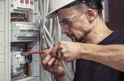 A male electrician works in a switchboard with an electrical con. Necting cable, connects the equipment with tools, the concept of complex work, space for text Stock Photography