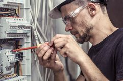 A male electrician works in a switchboard with an electrical con. Necting cable, connects the equipment with tools, the concept of complex work, space for text Royalty Free Stock Image