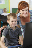 Male Elementary Pupil In Computer Class With Teacher Stock Photo