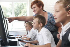 Male Elementary Pupil In Computer Class With Teacher Stock Photography