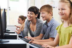 Male Elementary Pupil In Computer Class With Teacher. Elementary Pupil In Computer Class With Teacher Stock Images