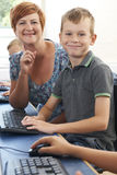 Male Elementary Pupil In Computer Class With Teacher. Portrait Of Male Elementary Pupil In Computer Class With Teacher Royalty Free Stock Images