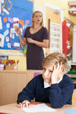 Male Elementary School Pupil Struggling In Class Stock Photo