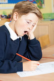 Male Elementary School Pupil Yawning In Classroom Stock Images