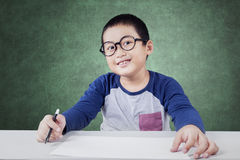 Male elementary school student with paper in class. Portrait of little schoolboy smiling on the camera while wearing glasses and holding a marker with empty Stock Image