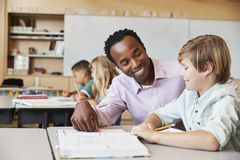 Male elementary school teacher and boy in class, close up stock photos