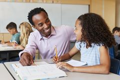 Male elementary school teacher and girl in class, close up stock photography
