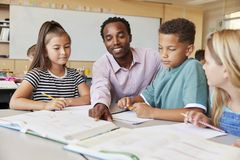 Male elementary school teacher working in class with kids royalty free stock photography