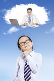 Male elementary student thinks dream job. Male elementary school student thinking dream job while looking up at speech bubble, shot outdoors Stock Images