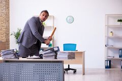 Young employee angry with excessive work holding baseball bat
