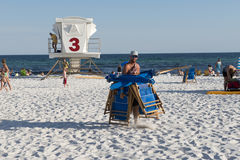 Male employee is carrying chairs back to storage at the end of the work day. Male employee carries beach chairs to store them at the end of a work day at the Stock Image