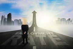 Male employee and employment rate text. Image of businessman with cardboard head, standing on the road shaped upward arrow with employment rate text Stock Photos