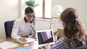 Male employee with telephone specifies information from woman opposite. Man with glasses asking a question at an employee in office behind a desk stock video footage