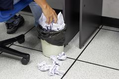 Male employee throwing crumpled white paper into trash in work office. Concept office life stock images