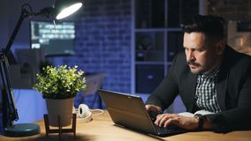 Male employee using laptop working overtime at night in office busy with project. Male employee bearded brunet is using laptop working overtime late at night in stock footage