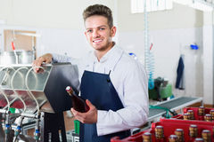 Male employee using machine to bottle wine. At sparkling wine factory Stock Photos