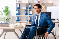 The male employee in wheelchair working at the office. Male employee in wheelchair working at the office royalty free stock photo