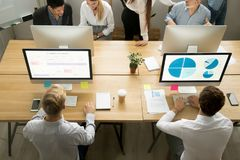 Employees using computers working with staff in office, top view. Male employees using computers for planning and data analysis sharing coworking desk working royalty free stock photo