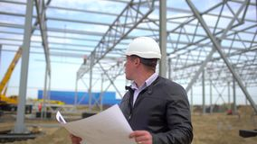 Male engineer architect supervisor in hard hats working with drawing blueprint and discussing plan, checking quality of. Object on construction site stock video