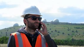 Male engineer or builder in a white helmet and talking on the phone, making a call. Against the backdrop of several