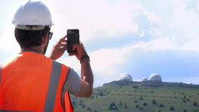 A male engineer or builder in a white helmet and vest makes a photograph of the observatory on the top of the mountain stock video footage