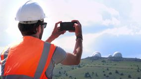 A male engineer or builder in a white helmet and vest makes a photograph of the observatory on the top of the mountain