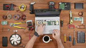 Male engineer computer repair works with disassembled laptop. One can see the computer`s motherboard. Wooden table top