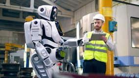 Male engineer is controlling movements of a robot stock video