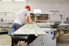 A male engineer controls the work of the machine in the furniture shop stock image