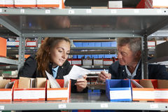 Male Engineer With Female Apprentice Checking Stock Levels. Engineer With Female Apprentice Checking Stock Levels royalty free stock photos