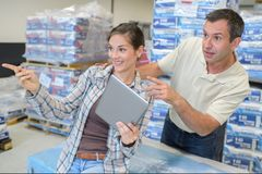 Male engineer with female apprentice checking stock levels. Male royalty free stock images