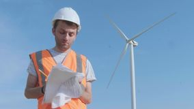 A male engineer fills documents in a field amid a wind turbine. Inspects the wind turbine with a copter. The concept of