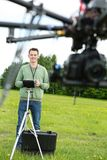 Male Engineer Flying UAV Octocopter. Young male engineer flying UAV octocopter with remote control in park Stock Photo