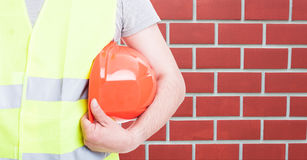 Male engineer holding helmet in closeup. Male engineer with protection vest holding helmet in closeup with copy text space Stock Image