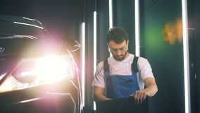 Male engineer is inspecting an automobile with his laptop stock video footage