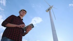 The male engineer is inspecting the wind turbine on the tablet. Sunny day and clouds. A man is dressed in a plaid shirt stock footage