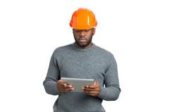Male engineer looking at computer tablet. Afro american young architect hold computer tablet on white background. Checking some information Stock Image