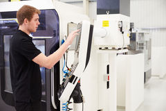 Male Engineer Operating CNC Machinery On Factory Floor Royalty Free Stock Photography