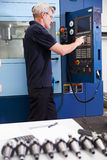 Male Engineer Operating CNC Machinery On Factory Floor Stock Photography