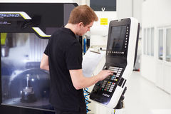 Male Engineer Operating CNC Machinery On Factory Floor Royalty Free Stock Photos