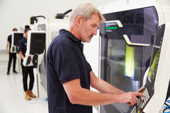 Male Engineer Operating CNC Machinery On Factory Floor Stock Photo