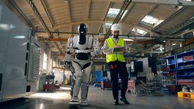 Male engineer and a robot are walking along the factory stock footage