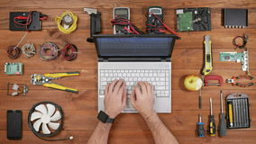 Male engineer software typing at his laptop and eating apple. Wooden table for electronics repair top view