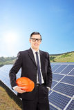 Male engineer standing in a field with solar panels Stock Photography