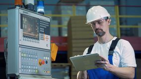 Male engineer with a tablet is standing near the control board. 4K stock video footage