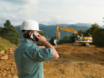 Male engineer talking on the phone. While supervising construction Stock Images