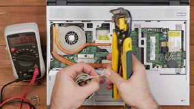 Male engineer to remove the insulation from the wire to repair the laptop. Wooden table top view. stock footage